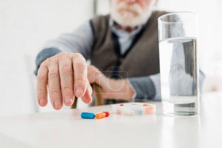 Photo pour Vue recadrée de l'homme âgé ramasser des pilules de la table - image libre de droit