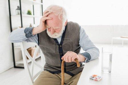 Photo for Depressed senior man with walking stick, sitting at home - Royalty Free Image