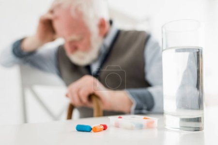 Selective focus of pills and water in glass on sad senior man background