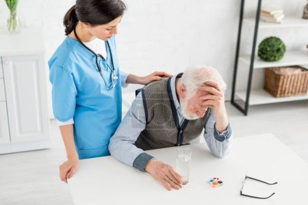 Photo for High angle view of nurse putting hands on sad grey haired man - Royalty Free Image