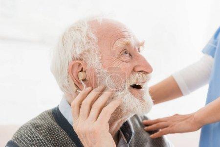 Photo pour Profil de l'homme heureux et gai avec l'aide auditive dans l'oreille, regardant loin - image libre de droit