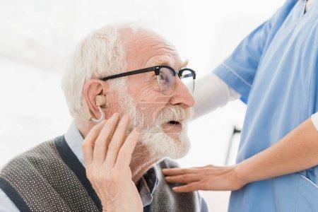 Photo pour Profil de l'homme barbu heureux avec l'aide auditive, regardant loin - image libre de droit