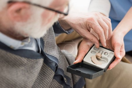 Photo for High angle view of elderly man looking at box with hearing aid - Royalty Free Image