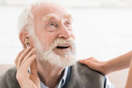 Photo pour Homme heureux avec l'aide auditive dans l'oreille, regardant loin - image libre de droit