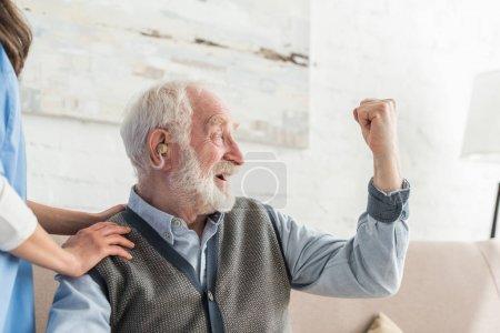 Photo pour Homme aîné heureux avec l'aide auditive regardant loin, s'asseyant à la maison - image libre de droit