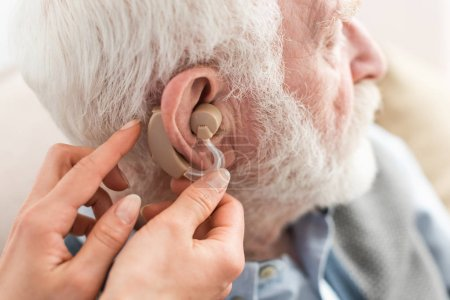 Photo pour Vue recadrée de femme aidant l'homme aux cheveux gris, portant l'aide auditive - image libre de droit