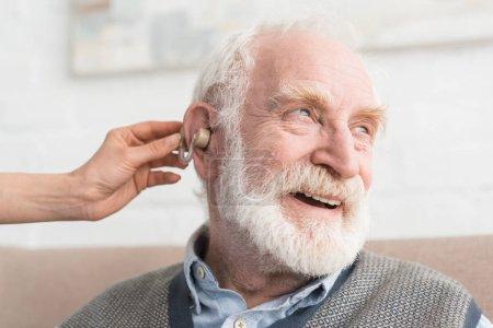 Photo pour Homme aux cheveux gris heureux avec l'aide auditive, et regardant loin - image libre de droit