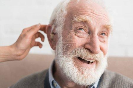 Photo pour Main de femme aidant l'homme aux cheveux gris, portant l'aide auditive - image libre de droit