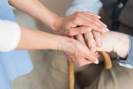 Cropped view of woman holding hands with senior man