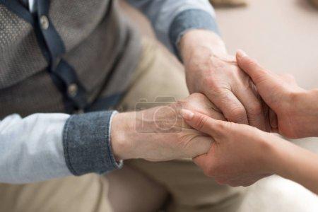 Photo pour Vue recadrée de la femme tenant la main avec un homme âgé - image libre de droit