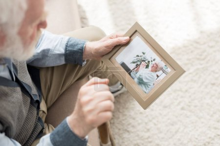 Photo for Retired man sitting on couch, and holding photo frame in hand - Royalty Free Image