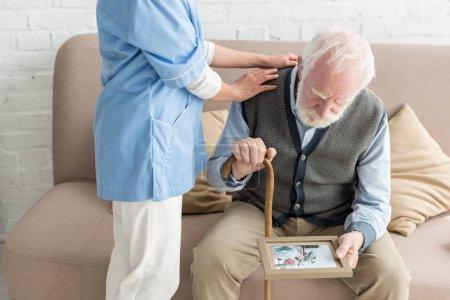 Photo pour Infirmière mettant la main sur l'homme de cheveux gris et bouleversé avec le cadre de photo - image libre de droit