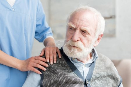 Photo for Nurse putting hands on shoulder of sad grey haired man - Royalty Free Image