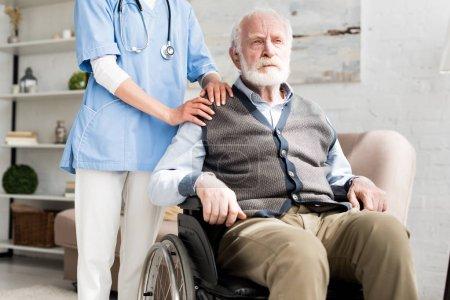 Photo pour Docteur mettant la main sur l'homme aîné handicapé dans le fauteuil roulant - image libre de droit