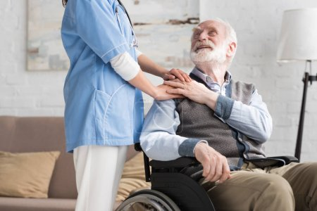 Photo for Happy and disabled senior man in wheelchair holding hands with doctor - Royalty Free Image