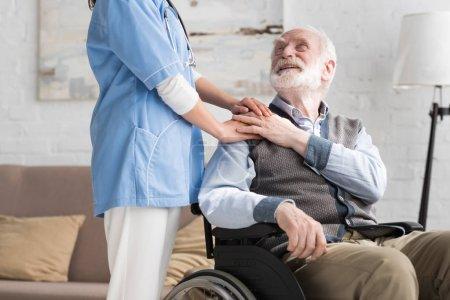 Photo pour Homme âgé heureux et handicapé en fauteuil roulant tenant la main avec un médecin - image libre de droit