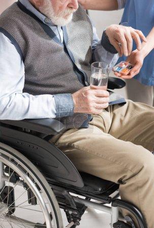 Photo pour Vue recadrée du médecin donnant des pilules à l'homme aîné handicapé dans le fauteuil roulant - image libre de droit