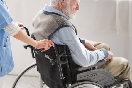 Photo for Cropped view of nurse standing behind disabled senior man in wheelchair - Royalty Free Image