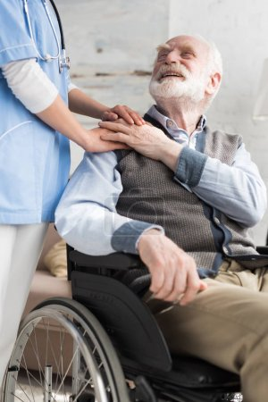 Doctor holding hands with cheerful and disabled senior man in wheelchair