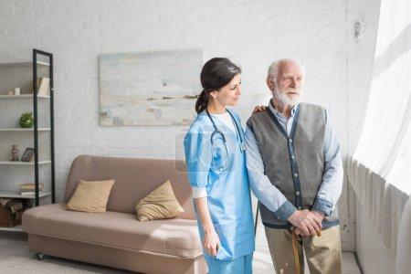 Photo pour Médecin regardant loin, debout avec l'homme aîné à l'intérieur de la maison avec l'espace de copie - image libre de droit