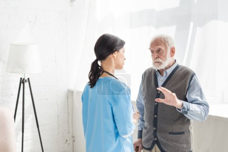 Photo pour Homme aîné restant à l'intérieur de la maison avec l'espace de copie, et parlant avec l'infirmière - image libre de droit