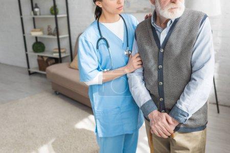 Photo pour Vue recadrée de l'homme aux cheveux gris debout avec infirmière dans une pièce lumineuse - image libre de droit