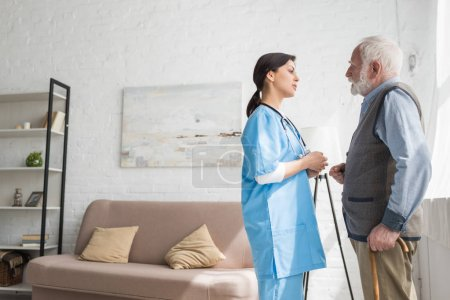 Photo for Grey haired man talking to nurse, standing in room with copy space - Royalty Free Image