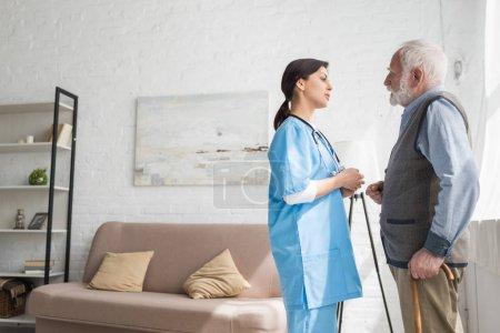 Photo pour Homme aux cheveux gris parlant à l'infirmière, restant dans la chambre avec l'espace de copie - image libre de droit