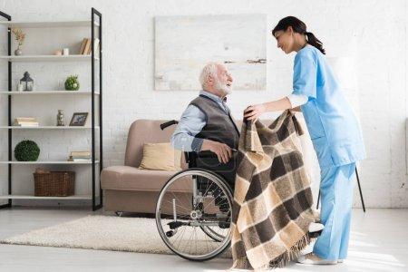 Photo pour Vue latérale de l'infirmière bienveillante, couverture handicapée et homme aux cheveux gris en fauteuil roulant - image libre de droit