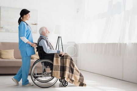 Photo for Side view of happy nurse standing in room with copy space, and carrying about disabled grey haired man in wheelchair - Royalty Free Image
