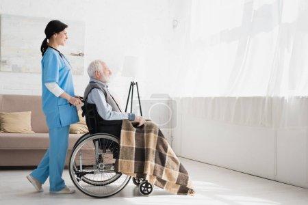 Photo pour Vue latérale de l'infirmière heureuse restant dans la chambre avec l'espace de copie, et transportant l'homme de poil gris handicapé en fauteuil roulant - image libre de droit