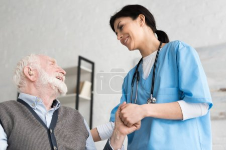 Low angle view of smiling doctor, holding hand with senior man
