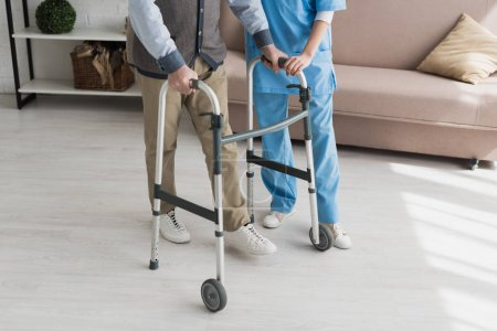 Photo for Senior man walking with nurse, and recovering from injury - Royalty Free Image