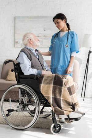 Photo for Nurse putting hands on disabled grey haired man in wheelchair - Royalty Free Image