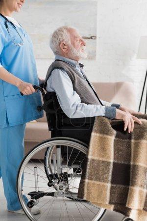 Photo pour Vue recadrée de l'infirmière portant sur handicapé et homme aux cheveux gris dans le fauteuil roulant - image libre de droit