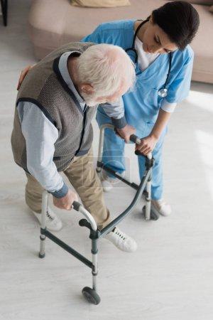 Photo pour Vue de grand angle du médecin aidant à la marche de l'homme aîné, récupérant après blessure - image libre de droit
