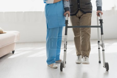 Photo for Cropped view of nurse walking with senior man in bright room - Royalty Free Image