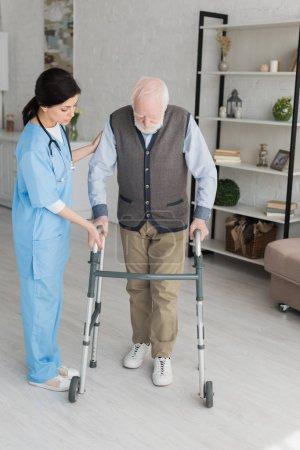 Photo pour Docteur aidant à la retraite d'homme marchant, et récupérant après blessure - image libre de droit