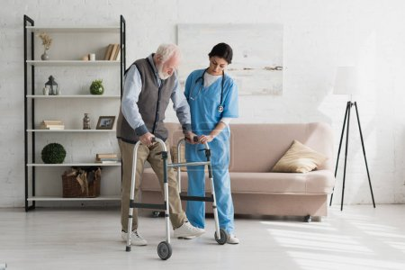 Photo for Nurse helping to senior man walking at home, recovering after injury - Royalty Free Image