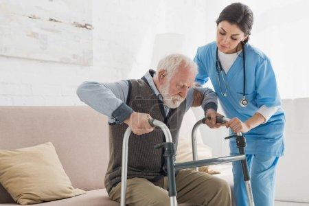Photo pour Docteur aidant à l'homme retraité, se lever du canapé - image libre de droit