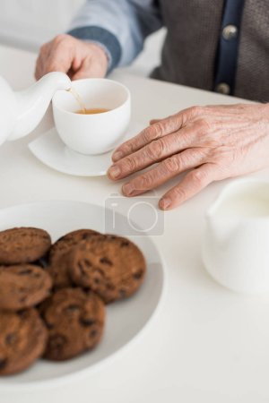Photo for Cropped view of senior man hand on white table with tea cup and cookies - Royalty Free Image