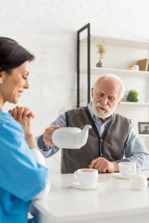 Photo for Cheerful nurse sitting on kitchen at home, while senior man pouring tea in cup - Royalty Free Image