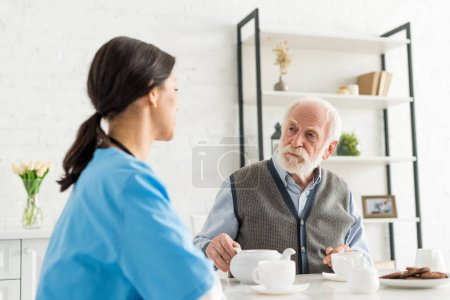 Photo for Calm grey haired man looking at nurse, sitting on kitchen at home - Royalty Free Image