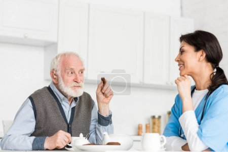 Cheerful grey haired man sitting on kitchen with cookie in hand, and looking at nurse
