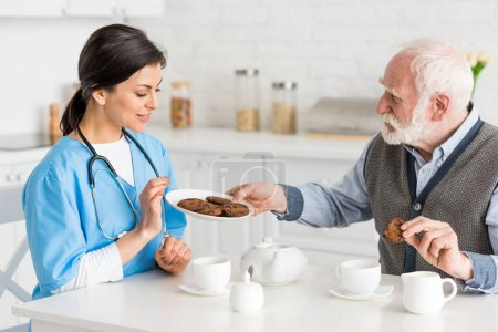 Photo for Grey haired man offering cookies to happy, and smiling nurse - Royalty Free Image