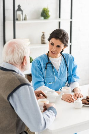 Photo for High angle view of nurse talking to gray haired man, sitting on kitchen - Royalty Free Image