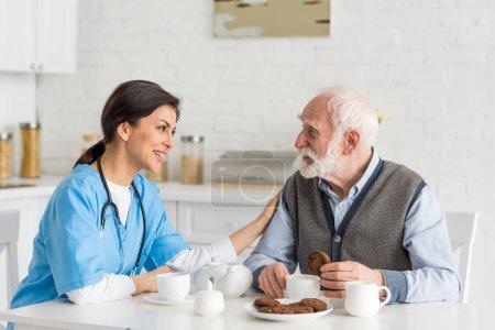 Photo pour Infirmière mettant la main sur l'homme aux cheveux gris, s'asseyant sur la cuisine - image libre de droit