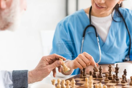 Photo for Cropped view of nurse and senior man sitting on kitchen, and playing in chess - Royalty Free Image