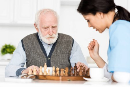 Photo for Selective focus on retired man sitting on kitchen, and playing in chess with nurse - Royalty Free Image