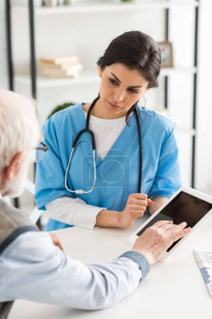 Photo for Cropped view of retired man sitting near doctor, and using digital tablet - Royalty Free Image
